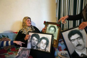 Milana al-Burji, 70, shows the pictures of her three children and husband who were killed in the Sabra and Shatila massacre, as she speaks to journalists in Sabra, Saturday, Jan. 11, 2014. (The Daily Star/Hasan Shaaban)