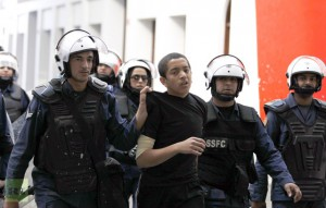 Riot police arrest a protester during an anti-government protest in the capital Manama