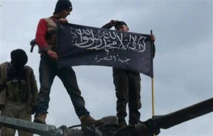 FILE - In this Friday, Jan. 11, 2013 file citizen journalism image provided by Edlib News Network, ENN, which has been authenticated based on its contents and other AP reporting, rebels from al-Qaida-affiliated Jabhat al-Nusra, also known as the Nusra Front, wave their brigade flag, as they step on the top of a Syrian air force helicopter at Taftanaz air base that was captured by the rebels in Idlib province, northern Syria. The Nusra Front, Syria's al-Qaida affiliate, is consolidating power in territory stretching from the Turkish border to central and southern Syria, crushing moderate opponents and forcibly converting minorities using tactics akin to its ultraconservative rival, the Islamic State group. (AP Photo/Edlib News Network ENN, File)