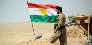 A peshmerga fighter stands next to a Kurdish flag as he guards a position near the strategic Jalawla area, in Diyala province, which is a gateway to Baghdad, as battles with Islamic State (IS) jihadists continue on August 25, 2014. Kurdish forces backed by Iraqi air support retook three villages in the Jalawla area, as well as a main road used by jihadists to transport fighters and supplies, peshmerga members said. AFP PHOTO / ALI AL-SAADI