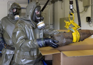 Workers dressed in protective clothing, hold a dummy chemical World War Two grenade, during a media demonstration at the Society for the Disposal of Chemical Weapons and Ordnance (GEKA) in Munster, March 5, 2014. The state owned GEKA is the only German company which is able to destroy chemical munitions and explosives. Syria has shipped out about a third of its chemical weapons, including mustard gas, for destruction abroad, the global chemical arms watchdog, the Organisation for the Prohibition of Chemical Weapons (OPCW) said on Tuesday. They are to be transferred to the U.S. ship MV Cape Ray and commercial destruction facilities in the United Kingdom and Germany, as part of a Russian-U.S. deal struck last year. REUTERS/Fabian Bimmer (GERMANY - Tags: MILITARY SCIENCE TECHNOLOGY) - RTR3G2KF