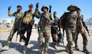 Iraqi fighters of the Shiite group Asaib Ahl al-Haq (The League of the Righteous) gesture upon their return to the southern city of Basra, on June 14, 2015. The group is fighting alongside Iraqi security forces against the Islamic State (IS) jihadist group in an attempt to try to retake the strategic northern town of Baiji. At least 11 members of the Iraqi security forces were killed the previous day near the town of Baiji in a series of suicide attacks claimed by IS jihadists. AFP PHOTO / HAIDAR MOHAMMED ALI