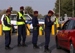 In this photo taken during a visit organized by Bahrain's Interior Ministry Bahrain police check a driver's identification at a checkpoint  in the capital of Manama, Bahrain  Monday, March 28, 2011. (AP Photo/Hasan Jamali)