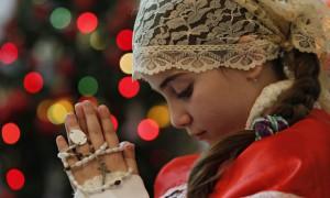 Holy fire … an Iraqi Christian girl prays in a Chaldean church in neighbouring Jordan