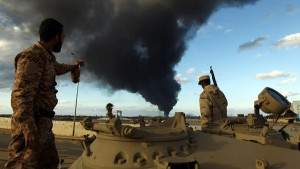 Members of the Libyan army stand on a tank as heavy black smoke rises from the city's port in the background after a fire broke out at a car tyre disposal plant during clashes against Islamist gunmen in the eastern Libyan city of Benghazi on December 23, 2014. Forces loyal to former general Khalifa Haftar and to internationally recognised Prime Minister Abdullah al-Thani have been battling for weeks against Islamists who have taken control of much of Libya's second city, and the capital Tripoli. AFP PHOTO / ABDULLAH DOMA