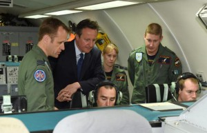 British Prime Minister David Cameron (2nd L) is given a tour of an E-3D Sentry aircraft aircraft by Wing Commander Steve Kilvington (L), during a visit to RAF Coningsby in Lincolnshire, central England on July 13, 2015. AFP PHOTO / POOL / JOE GIDDENS