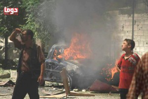 This photo provided by the Syrian anti-government activist group Douma Revolution, which has been authenticated based on its contents and other AP reporting, shows Syrian citizens look on as they stand in front of a burned car that set on fire by an attack of Syrian government airstrike, in Douma, a suburb of Damascus, Syria, Thursday, Aug. 20, 2015. An international human rights group called on the U.N. Security Council to impose an arms embargo on the Syrian government following airstrikes on a rebel-held suburb that killed more than 100 people. Many of those killed in the Aug. 16 attacks that targeted Douma's popular markets and residential areas were civilians. The New York-based Human Rights Watch said in a press release that the U.N. should also refer the situation in Syria to the International Criminal Court.(Douma Revolution via AP)