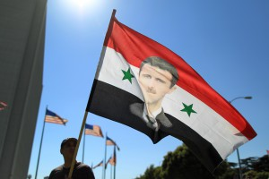 LOS ANGELES, CA - SEPTEMBER 7:  A supporter of Syrian president Bashar Hafez al-Assad waves a flag bearing a picture of the president at a rally to urge Congress to vote against a limited military strike against the Syrian military in response to allegations that Assad has used sarin gas to kill civilians on September 7, 2013 in Los Angeles, California. The Obama administration claims to have clear evidence that the Syrian military broke international law by killing nearly 1,500 Syrian civilians, including at least 426 children, in a chemical weapons attack on August 21, and is seeking the support of Congress for a missile strikes to prevent future chemical weapons attacks by the regime and other nations.   (Photo by David McNew/Getty Images)