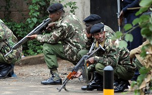 Armed Kenyan policemen take cover outside the Westgate mall in Nairobi on September 23, 2013. Kenyan troops were locked in a fierce firefight with Somali militants inside an upmarket Nairobi shopping mall on September 22 in a final push to end a siege that has left at least 69 dead and 200 wounded with an unknown number of hostages still being held. Somalia's Al Qaeda-inspired Shebab rebels said the carnage at the part Israeli-owned complex mall was in retaliation for Kenya's military intervention in Somalia, where African Union troops are battling the Islamists. AFP PHOTO / SIMON MAINA