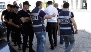 Police officers frisk an employee of the Koza Ipek Group during a raid at the company's office in Ankara, Turkey, September 1, 2015. Turkish police raided the offices of the conglomerate with close links to U.S.-based Muslim cleric Fethullah Gulen, an ally-turned-foe of President Tayyip Erdogan, company officials said on Tuesday.  REUTERS/Umit Bektas  - RTX1QKD8