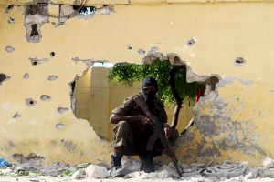 A Somali soldier takes position at the scene of a suicide attack by al Shabaab militants in capital Mogadishu June 21, 2015. Four Islamist gunmen were killed after detonating a car bomb and shooting their way into a national intelligence agency training site, the internal security ministry said, adding that the government did not suffer any casualties during the attack. REUTERS/Feisal Omar       TPX IMAGES OF THE DAY