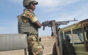 This photo taken on June 17, 2014 in Dabanga, northern Cameroon, shows a soldier standing guard by a machine gun, part of a convoy of Cameroon's army soldiers as part of a reinforcement of its military forces against Nigerian Islamist group Boko Haram. Boko Haram, which in April 2014 kidnapped more than 200 schoolgirls in northeast Nigeria to international condemnation, has been waging a brutal, five-year insurgency that has claimed thousands of lives. AFP PHOTO / REINNIER KAZE        (Photo credit should read Reinnier KAZE/AFP/Getty Images)