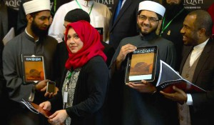 Leading Imams and scholars from Britain and Europe, from the left, Imam Asim Hussain, Sarah Warrick, Dr Qari Muhammad Asim and Shaykh Ahmad Babikir hold up various versions, online and printed of the new magazine 'Haqiqah' which translates as 'The Reality' and is aimed young people and to counter extremist views from groups such as Islamic State, at its official launch in London, Thursday, March, 26, 2015. (AP Photo/Alastair Grant)/XAG106/175149049793/1503261502