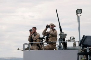 """Military personnel scan the horizon from on the deck of the Belgian Navy Vessel Godetia, one of the fleet of EU Navy Vessels taking part in the Triton migrant rescue operation, leaves the Sicilian harbour of Augusta on June 18, 2015.  EU border agency Frontex  launched its first so-called """"hotspot"""" in Sicily designed to bring together European and international actors to help Italy tackle the Mediterranean migrant crisis. Italy is struggling to cope with an influx of 60,000 migrants so far this year. Fleeing war or poverty, most arrive by sea from North Africa and many have died during the perilous journey in unsafe vessels run by people smuggling gangs.    AFP PHOTO / GIUSI COSENTINO"""