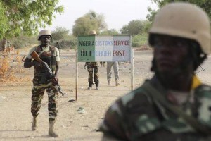 Nigerien soldiers walk past a customs signpost in Duji, Nigeria, March 25, 2015.   REUTERS/Joe Penney