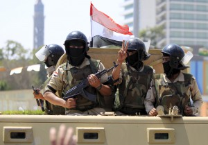 Army soldiers are seen as their convoy passes by Tahrir square to secure central Cairo as Egyptians celebrate an extension of the Suez Canal, in Cairo, Egypt, August 6, 2015. Egypt will open an expansion to the Suez Canal to great fanfare on Thursday, the centrepiece of President Abdel Fattah al-Sisi's plans to revitalise the country's economy after years of damaging political turmoil. REUTERS/Mohamed Abd El Ghany - RTX1NB4Q