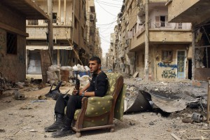 """A member of the Free Syrian Army holds his weapon as he sits on a sofa in the middle of a street in Deir al-Zor, in this April 2, 2013 file photo. The United States believes with varying degrees of confidence that Syria's regime has used chemical weapons on a small scale, the White House said on Thursday. But it added that President Barack Obama needed """"credible and corroborated"""" facts before acting on that assessment  REUTERS/Khalil Ashawi/Files  (SYRIA - Tags: CIVIL UNREST CONFLICT)"""