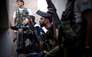 FSA fighters take cover from incoming Syrian Army fire in the Izaa district in Aleppo, Syria, Wednesday, Sept. 12, 2012. (AP Photo/ Manu Brabo)