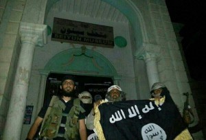 A picture taken with a mobile phone early on May 24, 2014 shows Al-Qaeda militants posing with the Al-Qaeda flag in front of a museum in Seiyun, second Yemeni city of Hadramawt province, after launching a massive pre-dawn assault that killed at least 15 soldiers and police. The assault in Hadramawt, a jihadist stronghold that has seen large-scale attacks on the army in the past, came as troops pressed a month-old ground offensive against Al-Qaeda in Abyan and Shabwa provinces to the west. AFP PHOTO / STR