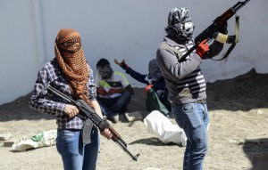 """Armed Kurdish militants of the Kurdistan Workers' Party (PKK) stand behind a barricade during clashes with Turkish forces on September 28, 2015, at Bismil, in Diyarbakir. Ankara launched a major """"anti-terrorist"""" campaign against the PKK in late July, aimed at flushing it out of its strongholds in southeastern Turkey and northern Iraq. AFP PHOTO / ILYAS AKENGIN        (Photo credit should read ILYAS AKENGIN/AFP/Getty Images)"""