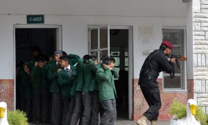 A Pakistani Elite Police Force member takes part in a drill to fight against militants at a school in Peshawar on January 28, 2016. A Pakistan university attacked by the Taliban last week has demanded the government arm its staff as it seeks to boost security after the deadly assault in which 21 people were killed, officials said. AFP PHOTO / A MAJEED