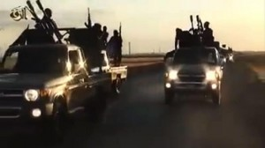 ATTENTION: These images were obtained on September 23, 2014 from YouTube on the Islamic State group's official media site, in a video posted for propaganda purposes. An image grab taken from a video released by Islamic State group's official Al-Raqqa site via YouTube on September 23, 2014, allegedly shows Islamist State (IS) group recruits riding in armed trucks in an unknown location. The US-led coalition launched strikes against Islamic State militants besieging a Kurdish town in Syria as world leaders prepared for talks on September 24, 2014 at the UN on battling IS. AFP PHOTO/HO/ Islamic State group's official Al-Raqqa site == RESTRICTED TO EDITORIAL USE - NO MARKETING NO ADVERTISING CAMPAIGNS - DISTRIBUTED AS A SERVICE TO CLIENTS FROM ALTERNATIVE SOURCES, AFP IS NOT RESPONSIBLE FOR ANY DIGITAL ALTERATIONS TO THE PICTURE'S EDITORIAL CONTENT, DATE AND LOCATION WHICH CANNOT BE INDEPENDENTLY VERIFIED ==
