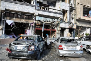 In this photo released by the Syrian official news agency SANA, Syrian citizens gather at the scene where twin bombs exploded at a government-run security checkpoint, at the neighborhood of Zahraa, in Homs province, Syria, Tuesday, Jan. 26, 2016. Homs governor Talal Barrazi said on Tuesday that a car bomb, which was followed by a suicide bomber wearing an explosive, killed more than a dozen people and injured many others. (SANA via AP)