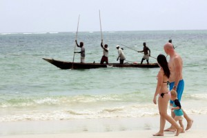 Tourists walk along the beach as fishermen paddle their boat near the shores of the Indian Ocean in the Kenyan coastal city of Mombasa, January 18, 2016. Kenya's tourism sector will take another two years to recover after the government beefed up security and boosted funding for the sector, a key source of hard currency revenues, new tourism minister Balala told Reuters. To match Interview KENYA-TOURISM/    REUTERS/Joseph Okanga