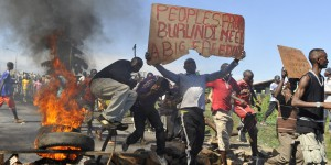 """Burundian men take part in a protest against the president's bid to cling to power for a third term in Musaga, outskirts of Bujumbura, on April 28, 2015. At least five people have died since clashes broke out on April 26 after the ruling CNDD-FDD party, which has been accused of intimidating opponents, designated President Pierre Nkurunziza its candidate in the June 26 presidential election.  On April 28, a spokesman for the President Nkurunziza said the President """"won't back down."""" AFP PHOTO / SIMON MAINA        (Photo credit should read SIMON MAINA/AFP/Getty Images)"""