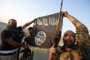 Iraqi Shiite militia fighters hold the Islamic State flag as they celebrate after breaking the siege of Amerli by Islamic State militants, September 1, 2014.  REUTERS/Youssef Boudlal (IRAQ - Tags: CIVIL UNREST POLITICS MILITARY TPX IMAGES OF THE DAY) - RTR44KEZ