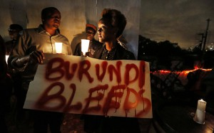 epaselect epa05068058 A Burundian expatriate woman holds a placard reading 'Burundi bleeds' during a candlelight vigil held for Burundi in Nairobi, Kenya, 13 December 2015. Kenyan activists and Burundians residing in Kenya held a candlelight service to call for peace in Burundi, that has been gripped by violence between police and armed groups since April, when President Pierre Nkurunziza announced he would seek a third term in office. Human rights activists say more than 240 people have been killed in protests and attacks since April, while more than 220,000 are believed to have fled the country.  EPA/DAI KUROKAWA