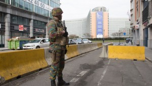 """A Belgian soldier stands guard at the Berlaymont building in Brussels, the headquarters of the European Commission, on March 22, 2016 near the Maalbeek subway station where an explosion occurred this morning. Belgian firefighters said on March 22 there were at least 21 dead after """"enormous"""" blasts hit Brussels airport and the city's metro system. / AFP / BELGA / HATIM KAGHAT / Belgium OUT        (Photo credit should read HATIM KAGHAT/AFP/Getty Images)"""