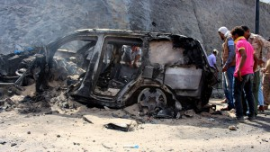 Yemenis inspect the scene of a car bomb attack that killed a Yemeni senior official in the southern port city of Aden, Yemen, Sunday, Dec. 6, 2015. A huge explosion killed the governor of Yemen's southern Aden province and six of his bodyguards on Sunday, security officials said, in an attack that was later claimed by a local Islamic State affiliate. (AP Photo/Wael Qubady)