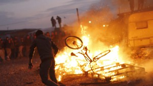 epaselect epa05602732 Migrants protest as workers dismantle the makeshift camp 'the Jungle' during its evacuation in Calais, France, 25 October 2016. The camp that held more than 7,000 migrants started being dismantled on 24 October, a process that shall take a week according tho the French authorities.  EPA/THIBAULT VANDERMERSCH