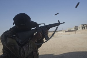 An Iraqi army soldier fires his rifle in the town of Shura, some 30 kilometers south of Mosul, Iraq, Saturday, Oct. 29, 2016. Iraqi troops approaching Mosul from the south advanced into Shura on Saturday after a wave of US led airstrikes and artillery shelling against Islamic State positions inside town. (AP Photo/Marko Drobnjakovic)
