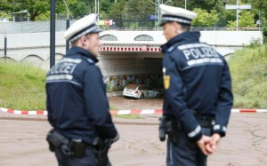 99442917_German_police_officers_stand_in_a_mud_covered_street_near_the_local_train_station_in_th-large_trans++DHhMJdyAdWy12tDbI1cVz6ppPHYoP0tKvCm5Nbw6FLo