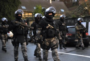 Members of the GIPN and RAID, French police special forces, walk in Corcy, northern France, on January 8, 2015 as they carry out searches as part of an investigation into a deadly attack the day before by armed gunmen on the Paris offices of French satirical weekly Charlie Hebdo. A huge manhunt for two brothers suspected of massacring 12 people in an Islamist attack at a satirical French weekly zeroed in on a northern town on January 8 after the discovery of one of the getaway cars. As thousands of police tightened their net, the country marked a rare national day of mourning for January 7's bloodbath at Charlie Hebdo magazine in Paris, the worst terrorist attack in France for half a century.   AFP PHOTO / FRANCOIS LO PRESTI        (Photo credit should read FRANCOIS LO PRESTI/AFP/Getty Images)