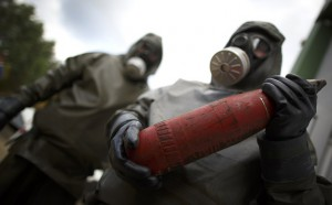 (FILES) This photo taken on October 30, 2013, shows employees in protective gear holding a dummy grenade during a demonstration at a chemical weapons disposal facility of GEKA (Gesellschaft zur Entsorgung von chemischen Kampfstoffen und Ruestungsaltlasten) in Munster, northern Germany. Syria has surrendered or destroyed nearly a third of its chemical arsenal but remains behind on its international obligations, the head of the disarmament mission told the world's chemical watchdog on March 4, 2014. Syria has already missed several target dates to hand over or destroy its arsenal before a June 30 deadline and the United Nations-Organisation for the Prohibition of Chemical Weapons (OPCW) mission called on Damascus to move faster. AFP PHOTO / PHILIPP GUELLAND