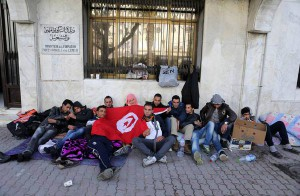 epa05162580 Unemployed Tunisians from city of Kasserine sit outside Tunisian Ministry of Vocational Training and Employment urging the government to provide them with job opportunities in Tunis, Tunisia, 15 February 2016. Protests erupted during January in the western central province of Kasserine against high unemployment, and soon spread to other areas including the capital, Tunis, forcing the government to impose a two-week night-time curfew.  EPA/MOHAMED MESSARA