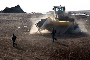 epa02505114 Israeli riot police accompany a bulldozer as it demolishes a bedouin living structure in the site of Al Akrib in the Negev Desert, near Beersheba, Israel on 23 December 2010. Israeli authorities have razed this 'unrecognized village,' which includes a cemetery, eight times as they try to get the Bedouins to move to the nearby Bedouin city of Rahat, something the Bedouins refuse to do, citing family deeds to this piece of land that pre-dates the establishment of the State of Israel.  EPA/JIM HOLLANDER
