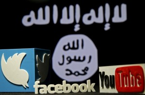 3D plastic representations of the Twitter, Facebook and Youtube logos are seen in front of a displayed ISIS flag in this photo illustration shot February 3, 2016. REUTERS/Dado Ruvic/File Photo