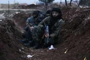 Members of al Qaeda's Nusra Front carry their weapons as they sit  in a trench near al-Zahra village, north of Aleppo city, November 25, 2014. Members of al Qaeda's Nusra Front and other Sunni Islamists seized an area south of the Shi'ite Muslim village in north Syria on Sunday after clashes with pro-government fighters, opposition activists said. The insurgents advanced overnight on al-Zahra, north of Aleppo city, seizing territory to the south and also trying to take land to the east in an attempt to capture the village, the Britain-based Syrian Observatory for Human Rights said. Picture taken November 25, 2014.  REUTERS/Hosam Katan    (SYRIA - Tags: POLITICS CIVIL UNREST CONFLICT TPX IMAGES OF THE DAY) - RTR4FOF2