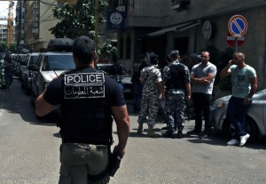 "Lebanese police intelligence gather outside a hotel after security forces raided there in Beirut's Hamra district, Lebanon, Friday, June 20, 2014. Security forces raided the hotel over suspected ""terrorist cells"" inside it, a police official said. In eastern Lebanon, a suicide bomber detonated his vehicle Friday near a police checkpoint, killing a few people amid heightened concerns of renewed violence, the country's state-run news agency and security officials said. (AP Photo/Bilal Hussein)"