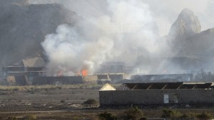 Buildings at the Jabal al-Hadid military camp burn as smoke rises in Aden, Yemen, Saturday, March 28, 2015. Yemeni military officials said an explosion rocked the camp that houses a weapons depot and had been taken by security forces loyal to ousted leader Ali Abdullah Saleh, killing and wounding several people. (AP Photo/Yassir Hassan)
