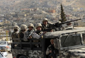 Lebanese army soldiers patrol on their armoured vehicle the Sunni Muslim border town of Arsal, in eastern Bekaa Valley March 20, 2014. The Lebanese army reopened a road between two towns near the Syrian border on Wednesday to try to calm sectarian rivalry aggravated by the conflict in neighbouring Syria. Shi'ite Muslims from the Bekaa Valley town of al-Labwa, where Hezbollah has strong support, had erected sandbag barriers at the weekend to cut off the Sunni Muslim town of Arsal from the rest of Lebanon. REUTERS/Hassan Abdallah (LEBANON - Tags: POLITICS CIVIL UNREST MILITARY) - RTR3HY4T